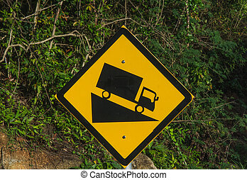 Steep road sign witah a truck driving down a steep downgrade in black and yellow on rainforest background Steep road sign with a truck driving down the abrupt slope. In black and yellow colors.