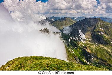Steep slope on rocky hillside in fog - edge of steep slope...
