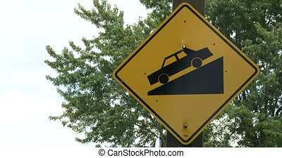 Steep slope road traffic sign with tree behind