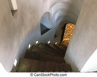 Steep stone spiral stairs going down from the steps.
