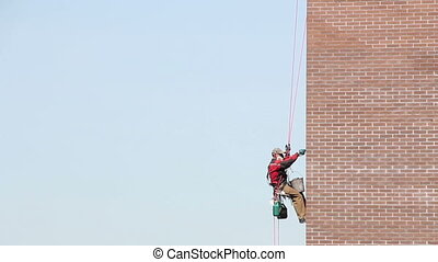 Steeplejack Builder worker plastering industrial building facade