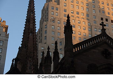 Steeples of an old church in New York City, with skyscrapers in the background.