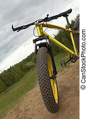 Steering of Fat bike at summer countryside - dirty bicycle, horizontal