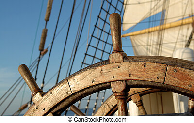 Steering wheel of the ship on the blue sky
