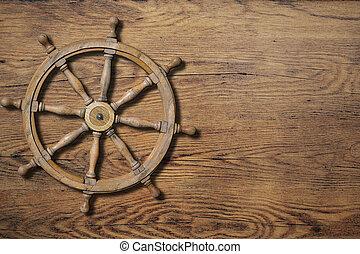 Steering wheel over wood background wall
