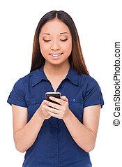 stehende , frau, beweglich, messages., junger, freigestellt, heiter, telefon, während, asiatisch, besitz, neu , lächeln, lesende , weißes