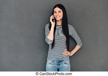 stehende , frau, talk., sprechende , beweglich, junger, gegen, grau, schauen, telefon, während, guten, attraktive, hintergrund, lächeln, sie