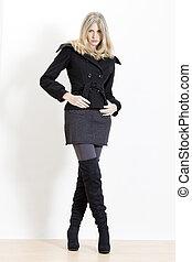 stehende , frau, tragen, modisch, schwarz, stiefeln