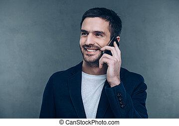 stehende , guten, talk., geschaeftswelt, sprechende , beweglich, grau, gegen, junger, heiter, telefon, während, hintergrund, lächelnden mann