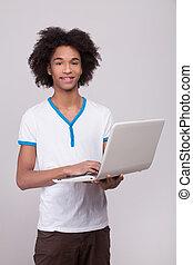 stehende , junge, jugendlich, arbeitende , grau, laptop, freigestellt, laptop., heiter, während, fotoapperat, teenager, hintergrund, afrikanisch, lächeln