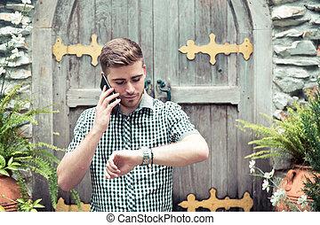 stehende , kleingarten, sprechende , -, uhr, hand, schauen, telefon, geld., zeit, mann