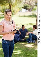 stehende , m�dchen, gebrauchend, a, smartphone