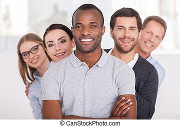 stehende , schauen, beibehaltung, team., gruppe, geschäftsmenschen, arme, junger, heiter, sicher, hinten, fotoapperat, während, afrikanisch, gekreuzt, lächelnden mann, ihm, reihe