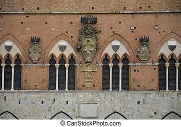 Particolare degli stemmi araldici sulla facciata del palazo comunale di Siena