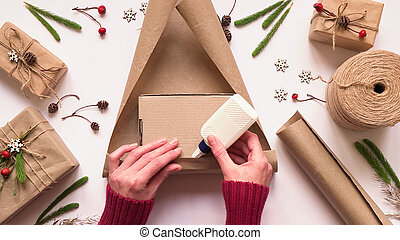 Step 2.Step by step instruction to eco friendly and zero waste Christmas gift wrapping.Woman wraps gift in brown paper and seals edges with glue,top view,flat lay.