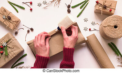 Step 3.Step by step instruction to eco friendly and zero waste Christmas gift wrapping.Woman wraps gift in brown paper and seals edges with glue,top view,flat lay.