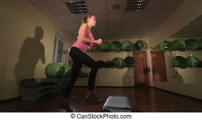 Step aerobics dance workout in fitness club