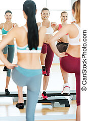 Step aerobics. Three beautiful young women in sports clothing doing step aerobics together and smiling while standing against mirror