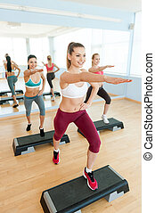 Step aerobics. Top view of three attractive young women in sports clothing doing step aerobics together and smiling