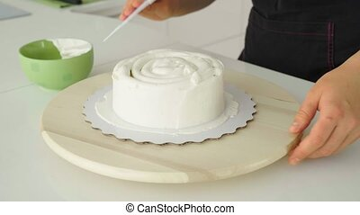 The confectioner covers the cake with cream.