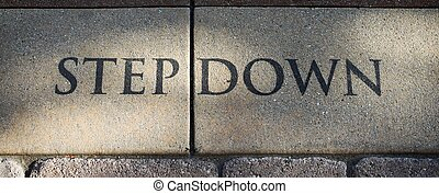 Step Down - Stone step Down sign on the ground.