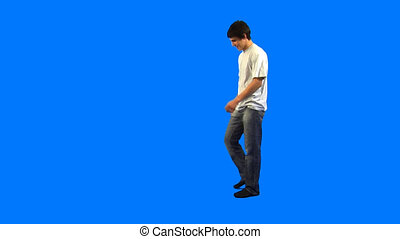 Handsome guy standing with raised leg on blue background in studio