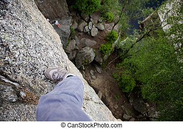 Step out on a Ledge - A foot on a ledge of a very high rock ...