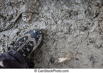 a man wearing a hiking boot stepping on a slimy mud surface