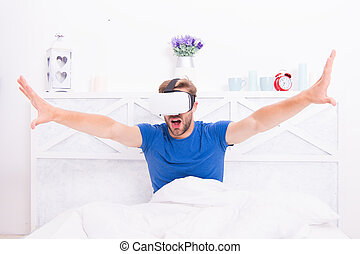 Stepping into the future. Handsome man wearing virtual reality headset in bed. Future vision. The future of entertainment and communication. Future concept