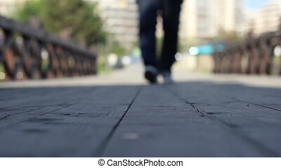 View from ground level with a man who tread on wearing sneakers, and passing over the viewer point of view.
