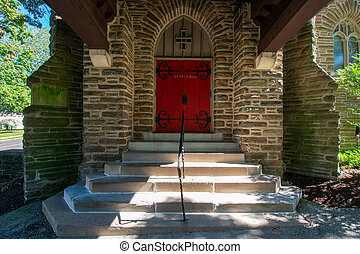 Steps Leading Up to a Red Door on a Cobblestone Church In a Covered Driveway
