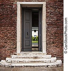 Steps to open door, doorway in old brick wall. Concept: way to the future, new opportunities