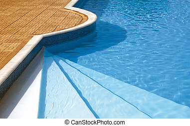 Steps to the swimming pool. Rippled water under sunlight