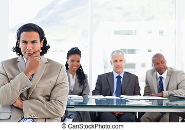 Stern businessman with his hand on his chin sitting in front of his business team