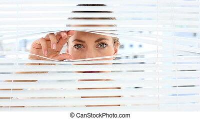 Stern businesswoman peeking through blinds - Stern...