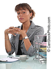 Stern businesswoman with coffee sat at desk