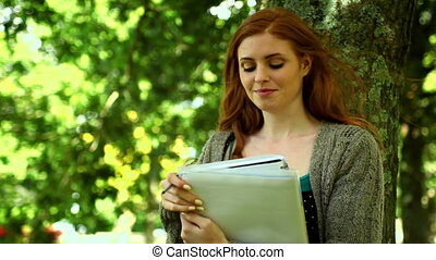 Stern content woman standing in park holding a notebook