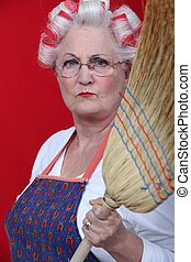 Stern elderly lady holding broom