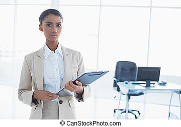 Stern elegant businesswoman holding clipboard - Stern...