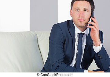Stern handsome businessman phoning and sitting on couch in...