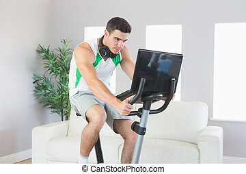 Stern handsome man training on exercise bike using laptop in...