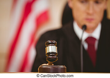 Stern judge about to bang gavel on sounding block in the...