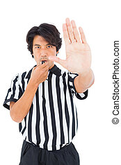 Stern referee showing stop sign with hand on white...