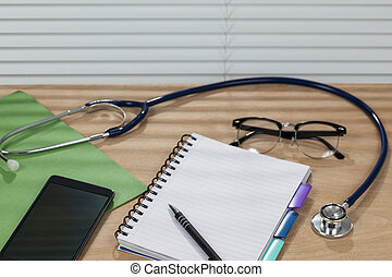 Stethoscope and a notepad laying on a doctors desk
