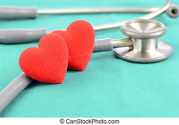 Stethoscope and hearts on green background in heart check up concept.