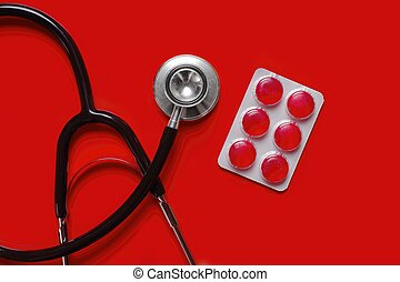 Stethoscope and medicine pills on red background with copy space.