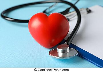 Stethoscope and red heart on blue background, close up. ...
