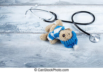 stethoscope and teddy bear on wood