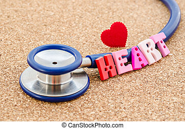 Stethoscope and the word heart with red heart.