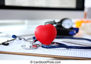 Stethoscope head and red heart shape toy lying on medical application form